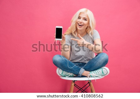 Cheerful woman sitting on the chair and showing blank smartphone screen over pink background - stock photo