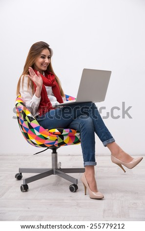 Cheerful woman sitting on the colourful chair and using laptop - stock photo