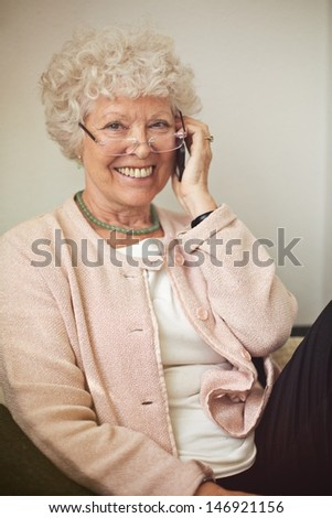 Cheerful woman smiling while calling on her cell phone - stock photo