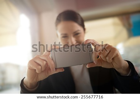 Cheerful woman taking a picture with her touch screen smartphone - stock photo