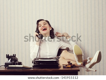 Cheerful woman talking on phone at desk - stock photo