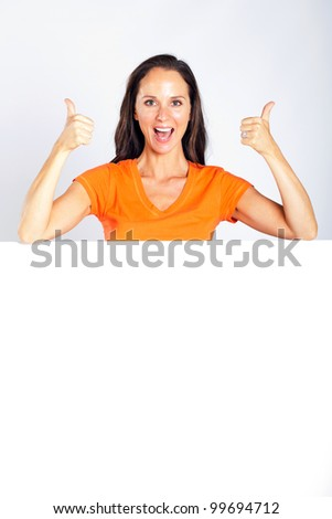 cheerful woman thumbs up with white board - stock photo