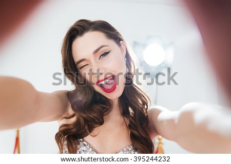 Cheerful woman winking and making selfie photo  - stock photo