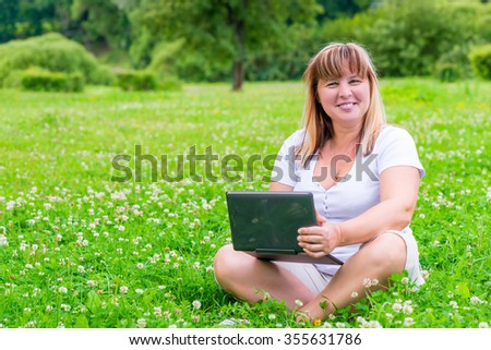 cheerful woman with a laptop on the summer meadow