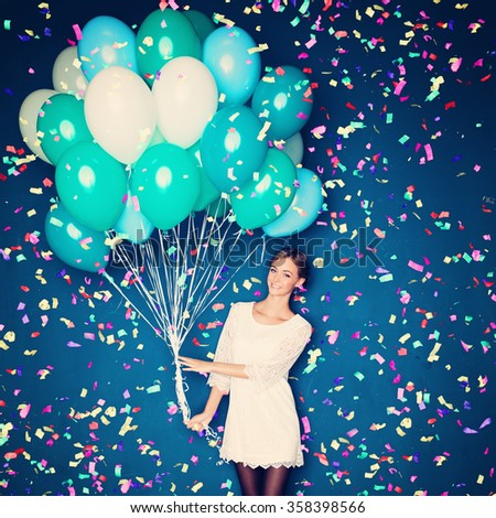 Cheerful Woman with  Balloons and Confetti on Blue Background - stock photo