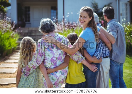Cheerful woman with family standing in back yard - stock photo