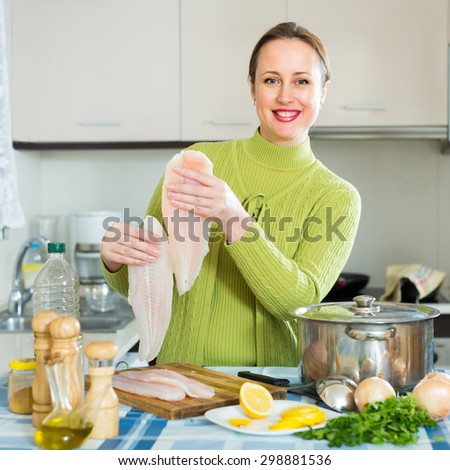 Cheerful woman with fish slices standing near boiling pan at kitchen - stock photo