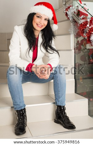 Cheerful woman with Santa hat sitting on stairs home in casual clothes