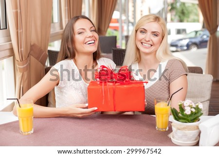 Cheerful women are giving a gift to each other in case of celebration. The brunette is holding a box of gift in her hands happily. The friends are smiling - stock photo