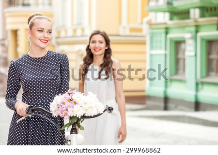Cheerful women are traveling across a town with bicycle. They are sightseeing and smiling. The friends are enjoying their trip. Copy space in right side - stock photo