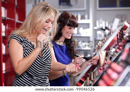 Cheerful women buying cosmetics in a beauty store - stock photo