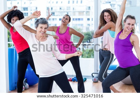 Cheerful women exercising with arms raised in fitness studio - stock photo