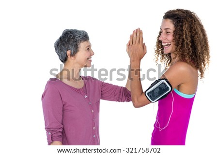 Cheerful women high fiving against white background - stock photo