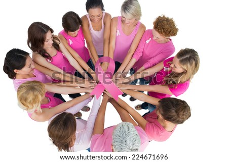 Cheerful women joined in a circle wearing pink for breast cancer against breast cancer awareness ribbon - stock photo