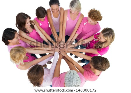 Cheerful women joined in a circle wearing pink for breast cancer on white background - stock photo