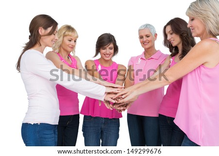 Cheerful women posing in circle wearing pink for breast cancer on white background - stock photo