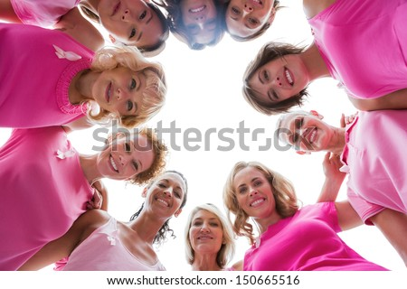 Cheerful women smiling in circle wearing pink for breast cancer on white background - stock photo