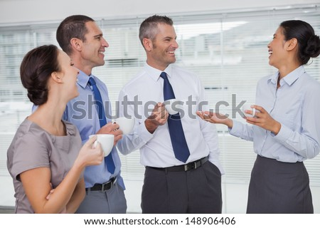 Cheerful work team during break time in bright office - stock photo