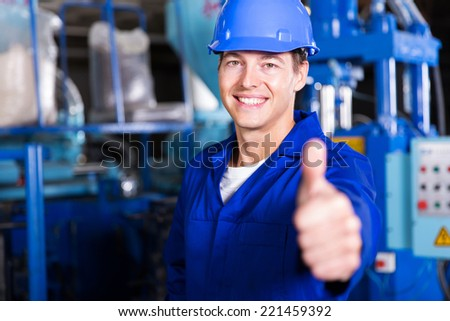 cheerful worker thumb up in factory - stock photo