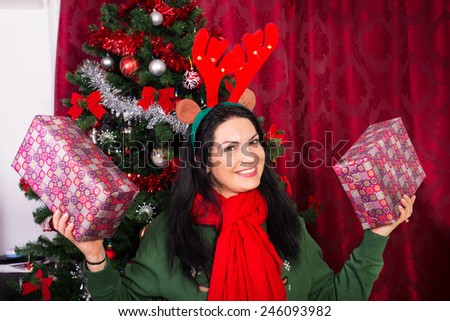 Cheerful Xmas woman with reindeer ears showing two Christmas gifts - stock photo