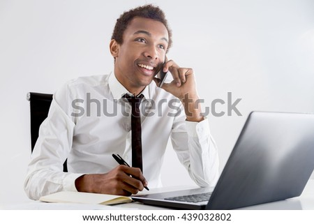 Cheerful young african american businessman having phone conversation while working at office desk on light background