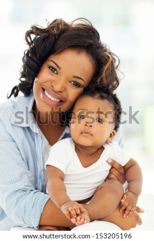 cheerful young african american mother holding baby girl