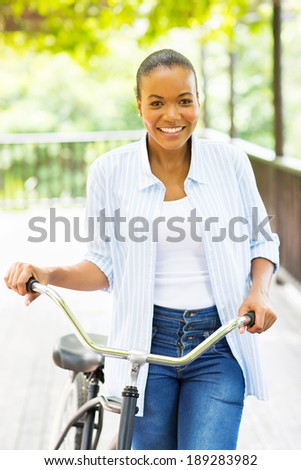 cheerful young african american woman walking with a bike outdoors - stock photo