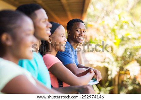 cheerful young african college boy with friends on campus - stock photo