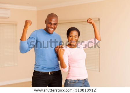 cheerful young african couple holding fist after buying a new apartment - stock photo