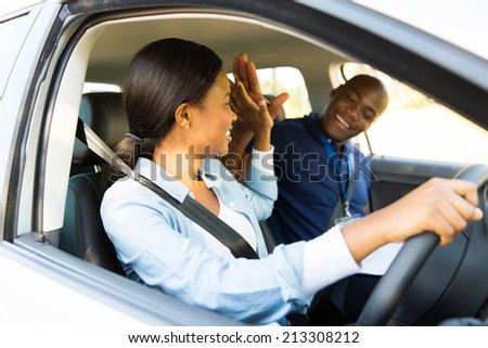 cheerful young african learner driver and driving instructor high five - stock photo