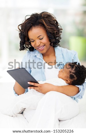 cheerful young african mother holding her baby while using tablet computer at home - stock photo