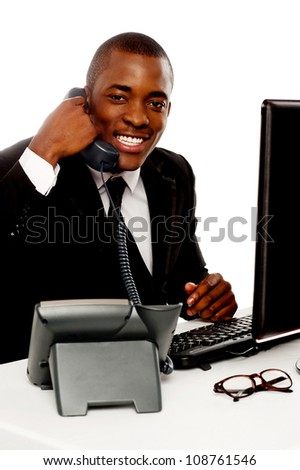 Cheerful young african talking on telephone against white background