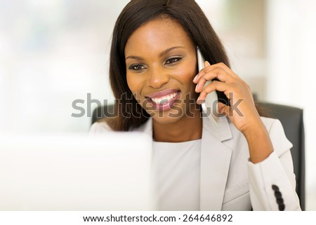 cheerful young afro american business woman talking on cell phone - stock photo