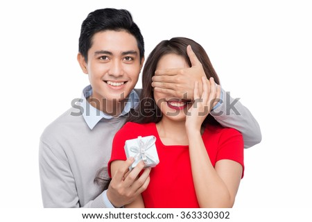 Cheerful young asian couple man and woman at home offering to each other gifts for lover's valentine day - stock photo