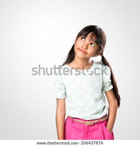 Cheerful young asian girl posing with looking up, studio shot - stock photo