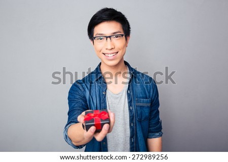 Cheerful young asian man in glasses giving gift box on the camera over gray background - stock photo