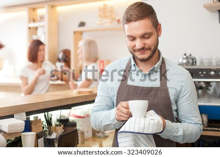 Cheerful young barista is working in coffee house. He is standing and drying a white cup with towel. He is looking at it and smiling. Two beautiful women are drinking coffee and talking on background - stock photo