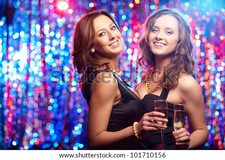 Cheerful young beauties with flutes of champagne having a nightclub party - stock photo