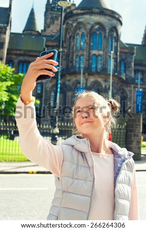 Cheerful young beautiful girl taking picture with smartphone in Glasgow historical place. Traveling. Summertime outdoors. - stock photo