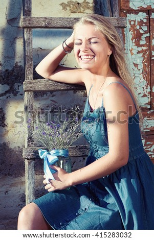 cheerful young blond woman sitting on the stairs in a blue dress with flowers and laughs - stock photo