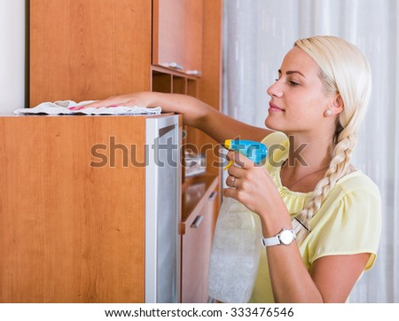 Cheerful young blonde girl dusting in room and smiling - stock photo