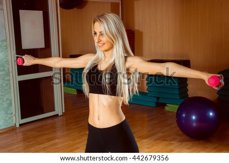 cheerful young blonde sports woman doing exercises in the gym with dumbbells in her hands - stock photo
