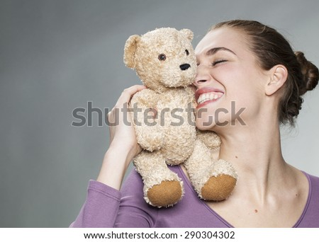 cheerful young blonde woman cuddling her teddy bear on her shoulder with tenderness for beautiful memories together - stock photo