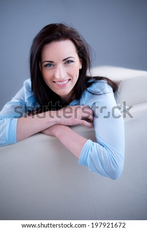 cheerful young brunette lying on her sofa relaxed at home  - stock photo