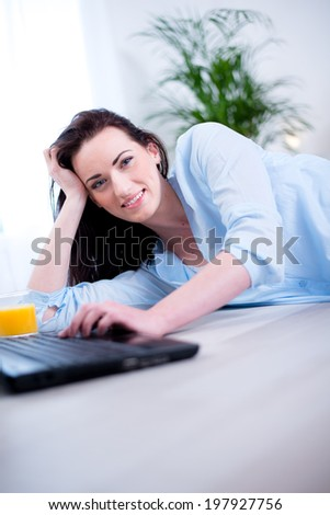 Cheerful young brunette lying on the floor at home with laptop relaxed - stock photo