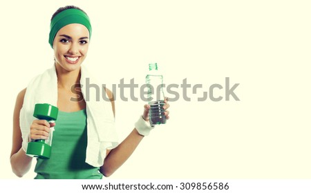 Cheerful young brunette woman in green fitness wear with dumbbell and water, with blank copyspace area for slogan or text - stock photo