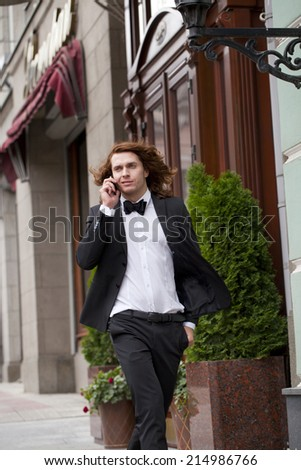 Cheerful young businessman calling by phone and walking summer street