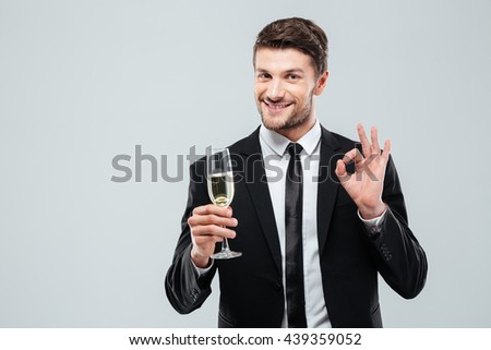 Cheerful young businessman drinking champagne and showing ok sign over white background - stock photo