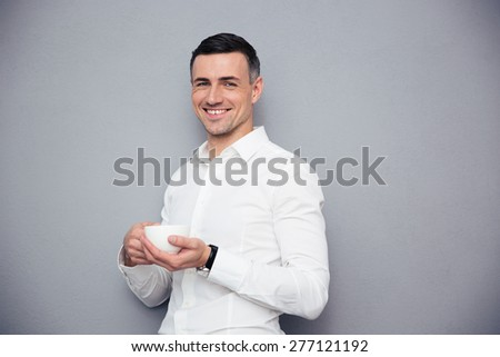 Cheerful young businessman holding cup of coffee over gray background and looking at camera