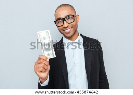 Cheerful young businessman in glasses holding dollar banknote - stock photo